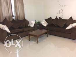 two brown sofas with cushions